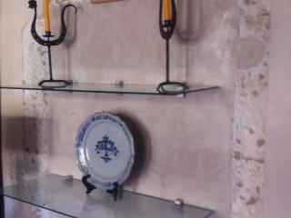 Mise en valeur de l'encadrement en pierre d'une ancienne porte, harmonisant le badigeon de chaux des murs et la chaux férrée de même couleur.